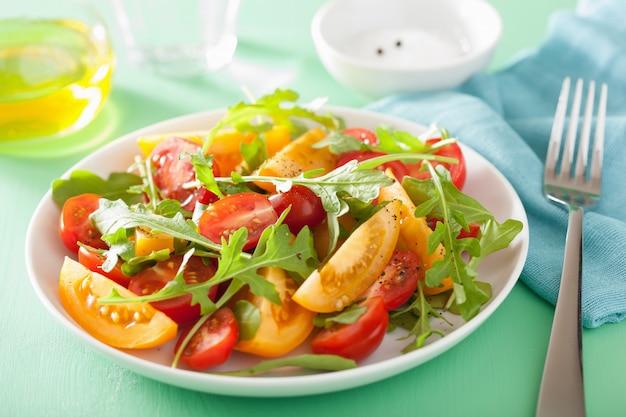 Ensalada de tomate con rúcula sobre mesa verde
