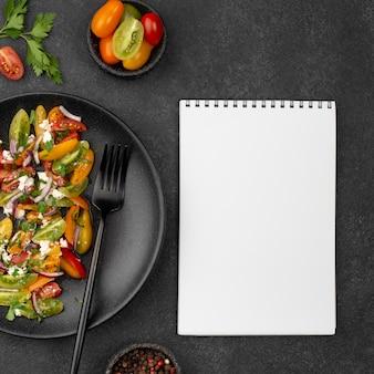 Ensalada de tomate vista superior con queso feta, rúcula y cuaderno en blanco