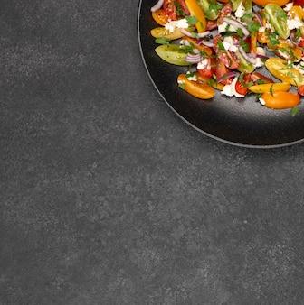 Ensalada de tomate vista superior con queso feta, rúcula y espacio de copia