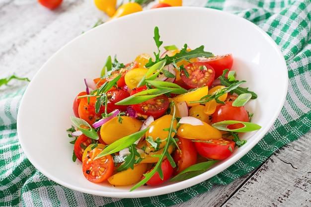 Ensalada de tomates cherry frescos con cebolla y rúcula