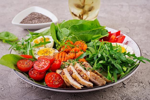 Ensalada con tomates cherry, pechuga de pollo, huevos, zanahoria, rúcula y espinacas