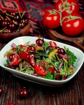 Ensalada de tomates, hierbas, cebollas y cerezas en salsa de soja