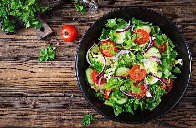 Ensalada de tomates, pepino, cebollas rojas y hojas de lechuga.