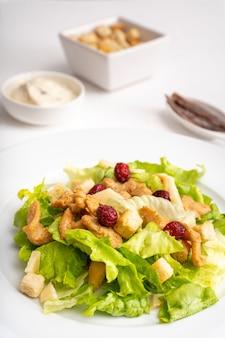 Ensalada con tostadas, anchoas y salsa sobre planta blanca y fondo blanco.