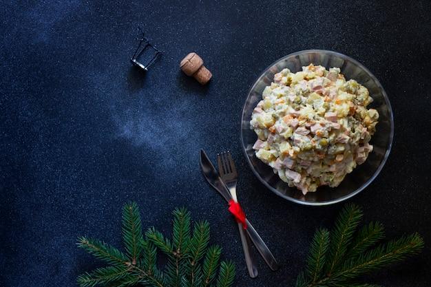 Ensalada tradicional de año nuevo ruso y navidad de verduras, carne y mayonesa llamada olivier. ensalada rusa. vista superior. fondo oscuro copyspace