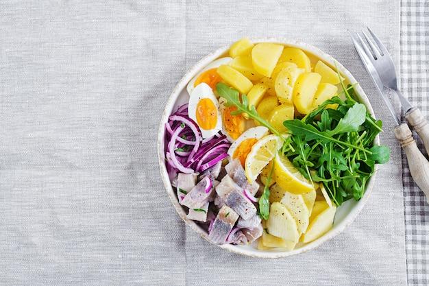 Ensalada tradicional de filete de arenque salado, huevos, manzanas frescas, cebolla roja y papas.