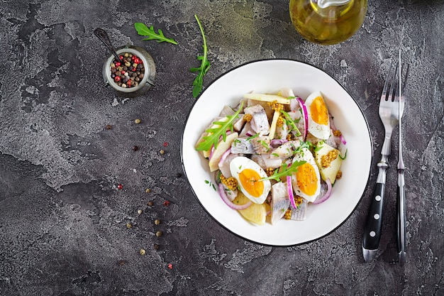 Ensalada tradicional de filete de arenque salado, manzanas frescas, cebolla morada y huevos.
