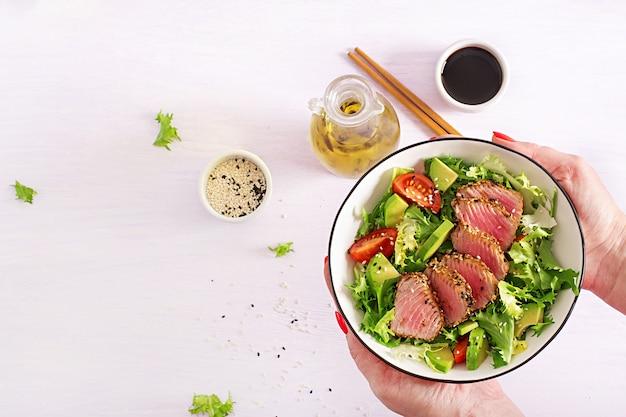 Ensalada tradicional japonesa con trozos de atún ahi a la parrilla medio raro y sésamo con ensalada de vegetales frescos en un plato.