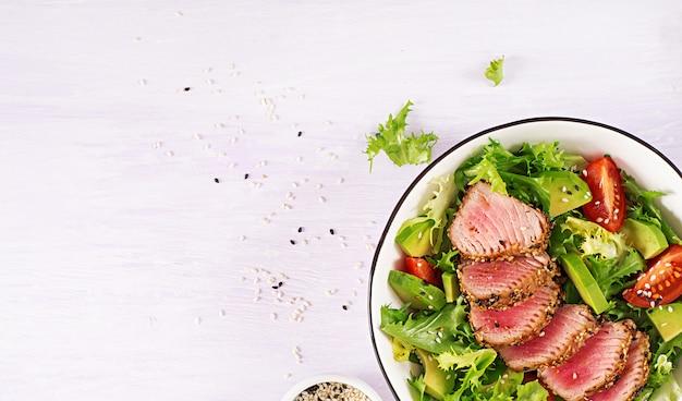 Ensalada tradicional japonesa con trozos de atún ahi a la parrilla medio raro y sésamo con vegetales frescos en un tazón.