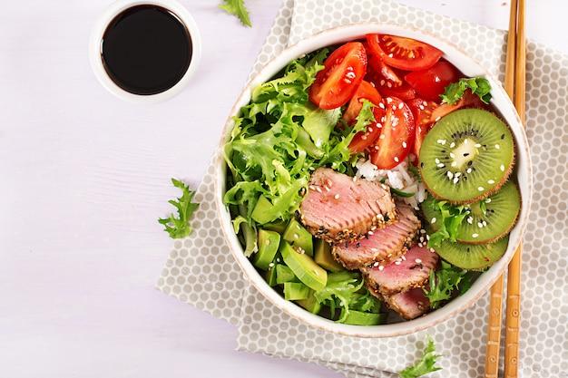 Ensalada tradicional con trozos de atún al ají a la plancha y sésamo a la parrilla poco comunes con ensalada de verduras frescas