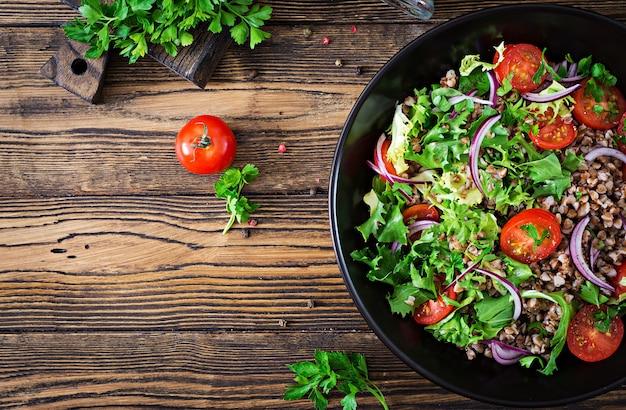 Ensalada de trigo sarraceno con tomates cherry, cebolla roja y hierbas frescas. comida vegana. menú de dieta vista superior. lay flat