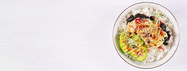 Ensalada vegana con arroz, col de kimchi en escabeche, aguacate, nori y sésamo en un tazón.