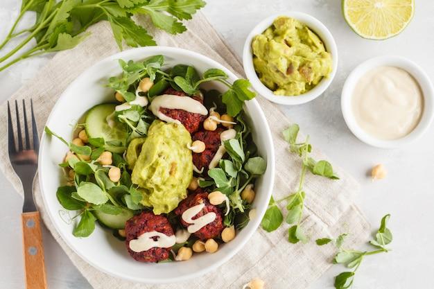 Ensalada vegana de vegetales verdes con albóndigas de remolacha, guacamole y aderezo de tahini. concepto de comida vegetariana saludable. copia espacio, vista superior