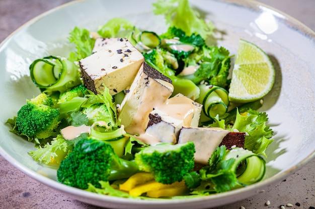 Ensalada vegana verde con brócoli, tofu ahumado y aderezo de tahini en un bol blanco,