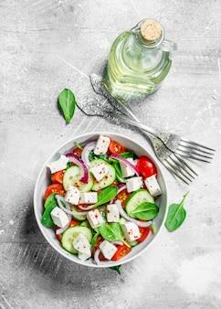 Ensalada de vegetales. ensalada de verduras, queso y aceite de oliva. sobre un rústico.