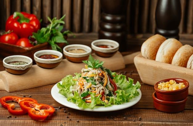 Ensalada de vegetales finamente picada que contiene zanahorias, repollo, tomates, pepino y ensalada