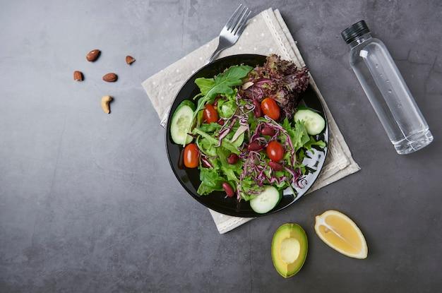 Ensalada de vegetales frescos y saludables con tomate, pepino, espinacas, le