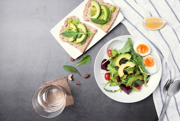 Ensalada de vegetales saludables frescos con huevo, tomate, aguacate, espinacas, lechuga en placa en el fondo de la tabla.