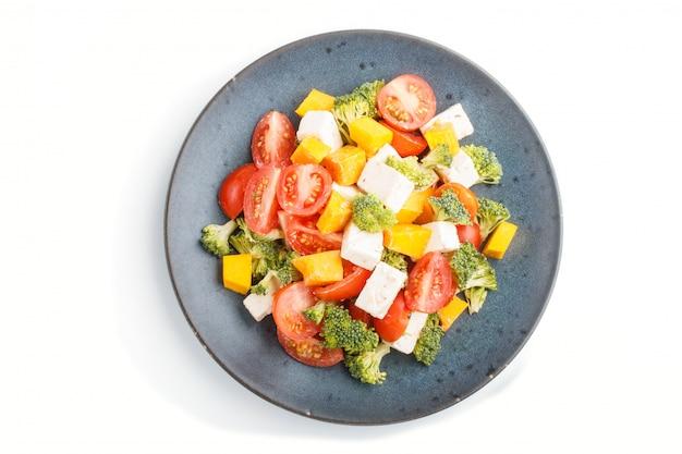 Ensalada vegetariana con brócoli tomates queso feta y calabaza en un plato de cerámica azul aislado sobre fondo blanco.