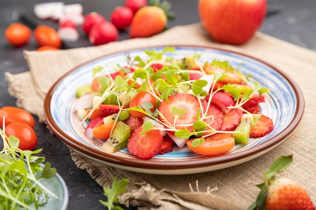 Ensalada vegetariana de frutas y verduras de fresa, kiwi, tomate, brotes microgreen sobre fondo de hormigón negro.