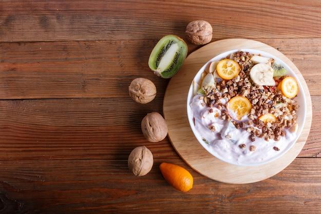 Ensalada vegetariana de plátanos, manzanas, peras, kumquats, kiwi con granola y yogur en madera marrón