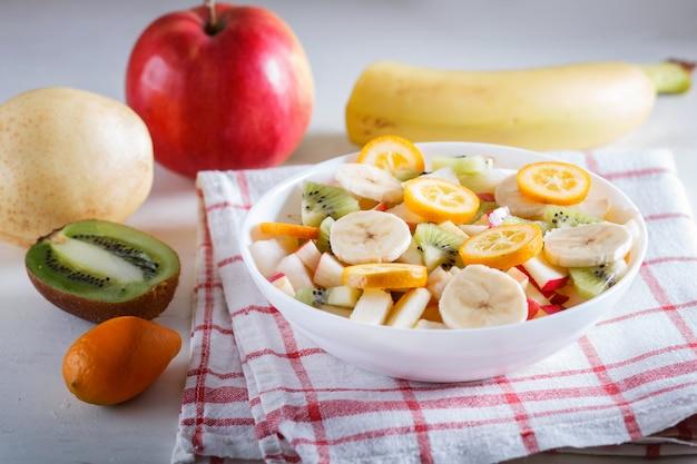 Ensalada vegetariana de plátanos, manzanas, peras, kumquats y kiwi sobre mantel de lino