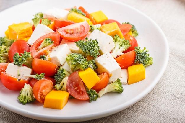 Ensalada vegetariana en plato de cerámica blanca sobre hormigón gris