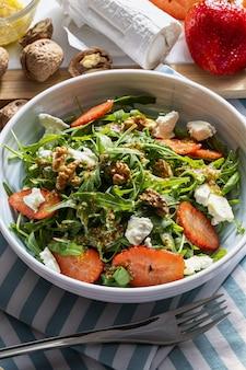 Ensalada vegetariana y saludable de brotes de rúcula rgula verde cruda y fresca y hojas de brassicaceae con fresas frescas nueces queso de cabra y aceite de oliva comida de la dieta mediterránea