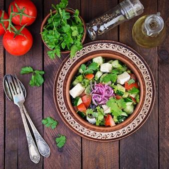 Ensalada vegetariana con tomate cherry, queso brie, pepino, cilantro y cebolla roja. cocina americana. vista superior. lay flat