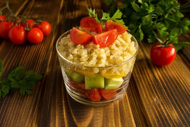 Ensalada vegetariana con verduras y quinua en la mesa de madera marrón