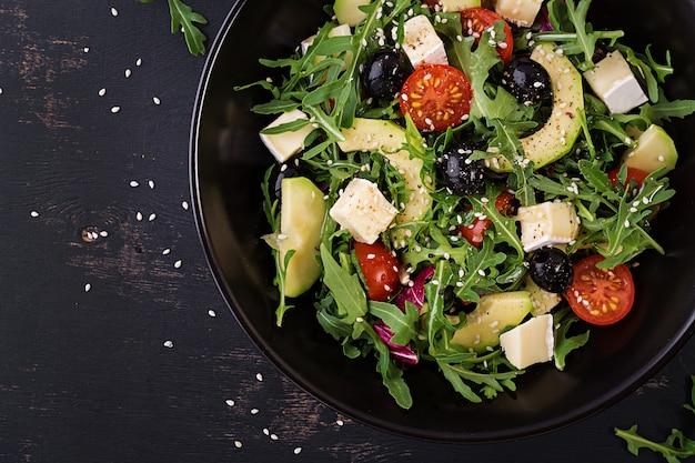 Ensalada verde con aguacate en rodajas, tomates cherry, aceitunas negras y queso