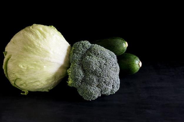 Ensalada verde de brócoli y calabacín fresco sobre una mesa negra, estilo rústico, clave oscura.