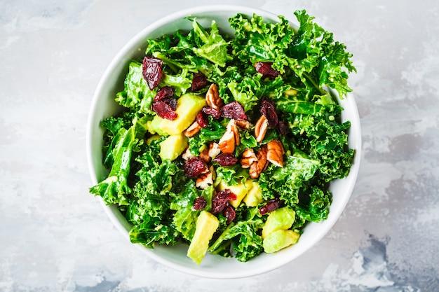 Ensalada verde de la col rizada con los arándanos y el aguacate en el tazón de fuente blanco, visión superior. concepto de comida vegana saludable.
