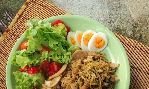Ensalada verde fresca con fideos salteados y huevo cocido