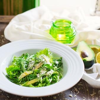 Ensalada verde con lechuga, aguacate, rúcula y queso parmesano