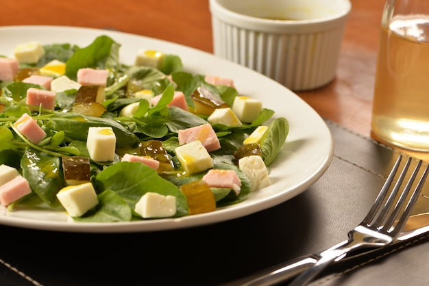 Ensalada verde con queso fresco, jamón y pepinillo.