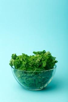 Ensalada verde en un recipiente de vidrio sobre fondo azul.