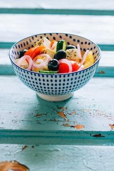 Ensalada de verduras y aceitunas con palillos sobre fondo azul de madera
