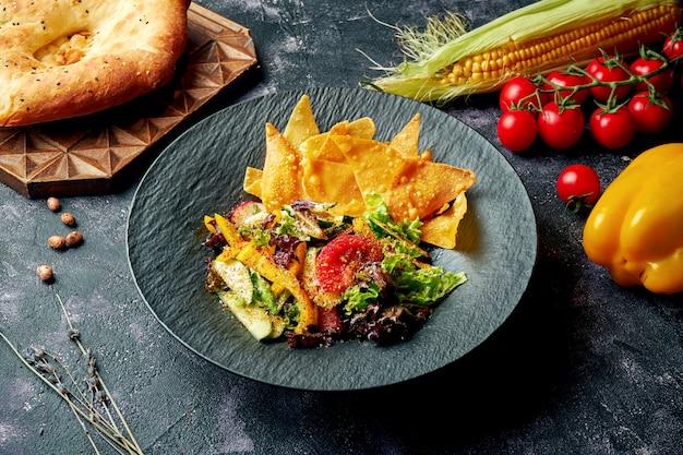 Ensalada de verduras al estilo oriental con especias y nacho en cuenco negro. fattoush - ensalada de pan levantino,