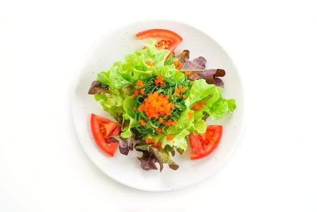 Ensalada de verduras con algas japonesas y huevos de camarón en mesa blanca