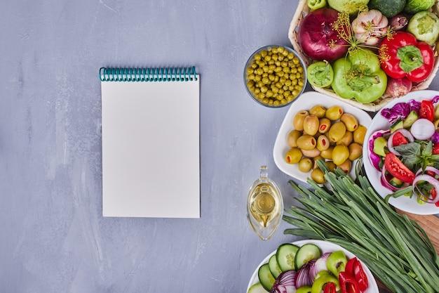 Ensalada de verduras con alimentos en rodajas y picados y un libro de recetas a un lado.