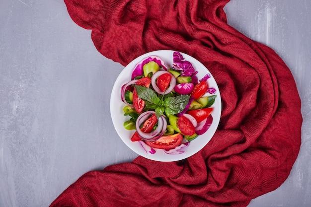 Ensalada de verduras con alimentos en rodajas y picados en un plato blanco.