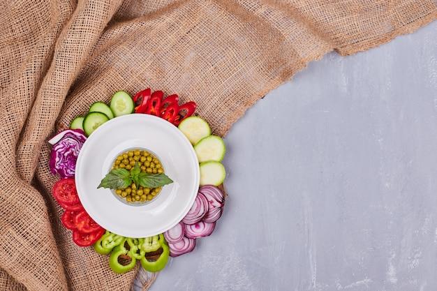 Ensalada de verduras con alimentos en rodajas y picados y una taza de guisantes, vista superior.