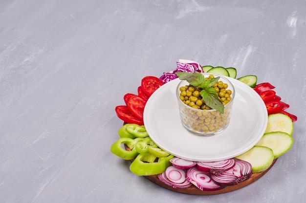 Ensalada de verduras con alimentos en rodajas y picados y una taza de guisantes.