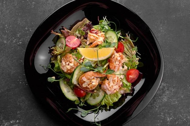 Ensalada de verduras con camarones, sobre un fondo negro