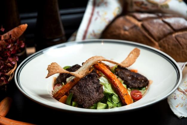 Ensalada de verduras con carne a la parrilla y zanahorias fritas
