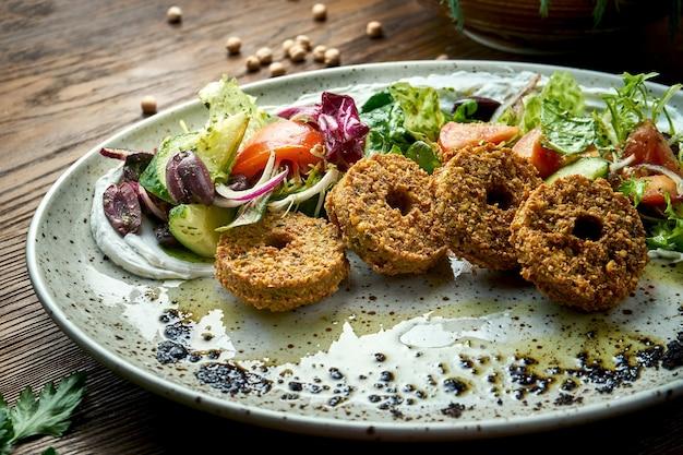 Ensalada de verduras con falafel y aceite de oliva servida en un plato azul sobre un fondo de madera. comida de restaurante