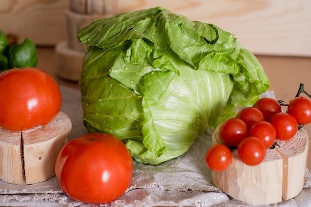 Ensalada de verduras frescas de col, pepino, tomate con aceite de oliva o girasol en la mesa de madera.