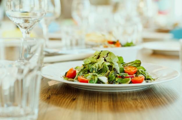 Ensalada de verduras frescas y hierbas con pesto sobre la mesa en el restaurante.