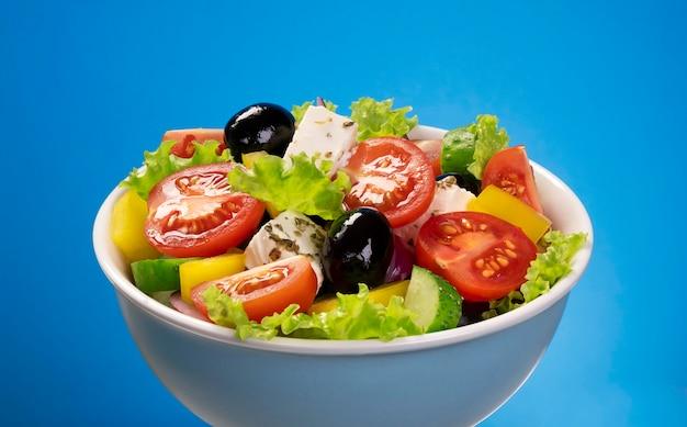 Ensalada de verduras frescas, ingredientes de la cocina mediterránea, ensalada griega en azul